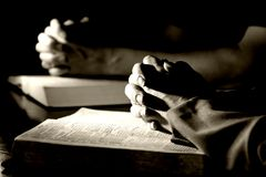 Man & Woman Praying Bibles (BW). A man and woman pray together with their hands resting upon Holy Bibles - high contrast black and white (Christian Image Royalty Free Stock Photography