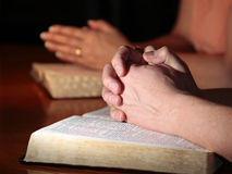 Man and Woman Praying with Holy Bibles. A man and woman (or couple) praying together with their Holy Bibles open under their hands (focus on man's foreground stock photos