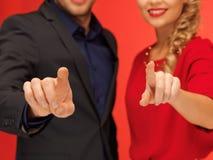 Man and woman pressing virtual button Stock Photos