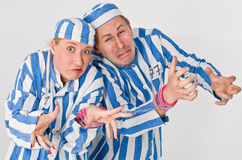 Man and woman prisoners. A view of expressive actors dressed in blue-striped prison shirts and hats stock photo