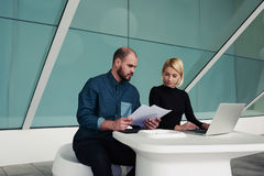 Man and woman professional bookkeepers working together with reports and net-book Stock Image