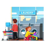 Man and woman in public self service laundromat. Laundromat self service. Man rolling wheeled laundry basket or cart and woman loading clothes to the washing Stock Photography