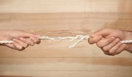 Man and woman pulling frayed rope at breaking point. On wooden background stock photo