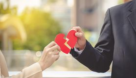Man and woman pulling a red paper heart apart. The concept of un. Requited love. Broken heart royalty free stock images
