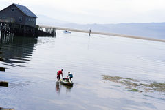 Man and woman pulling rubber boat on backwater of ocean with woo Stock Photography