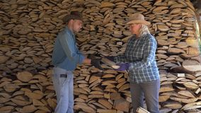 A man and a woman put together firewood in the woodshed helping each other. A cowboy man and a mature woman on a ranch in a woodshed together carefully fold stock video