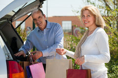 Man and woman putting bags  in car trunk Stock Images