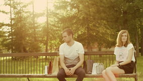 Man and woman after quarrel. Man and woman sit on the bench in the park turned away from each other after quarrel stock footage