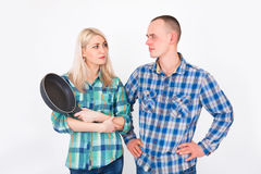Man and woman quarrel. A woman with a frying pan in his hands. Stock Image