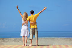 Man and woman on quay lifted hands upwards Royalty Free Stock Image