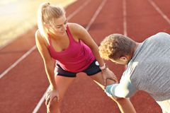 Man and woman racing on outdoor track stock image