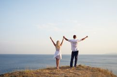 Man and woman raising their hands to the sky Stock Images
