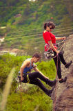Man and woman rapelling down mountain Stock Photo