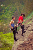 Man and woman rapelling down mountain Royalty Free Stock Photos
