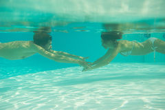 Man and woman reaching out for each other under water Stock Photo