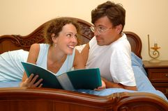 Man and woman read. On bed Stock Images