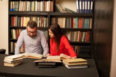 A man and a woman reading a book in the library before the exam stock image