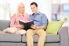 Man and woman reading a book seated on sofa Stock Photos