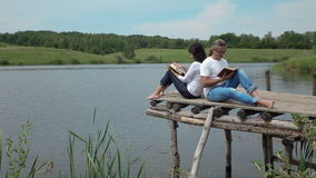 Man and woman reading books on the board table near lake stock video footage