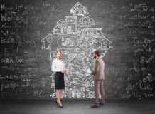 Man, woman and real estate sketch. Portrait of a male and female real estate agents standing near a blackboard with house market icons on it Royalty Free Stock Photos