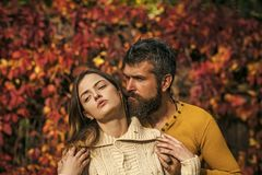 Man and woman at red tree leaves. Man and women at red tree leaves. Couple in love in autumn park. Autumn happy couple of girl and men outdoor. Love royalty free stock photography