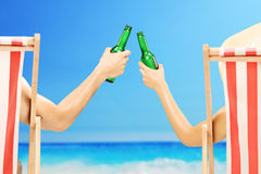 Man and woman relaxing on a beach and cheering with beer Royalty Free Stock Images