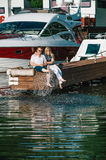 Man and woman relaxing on a berth in yacht club. Stock Photos