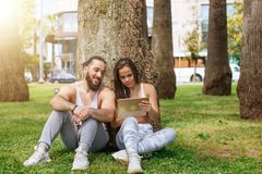 Man and woman relaxing with digital tablet in park after sports training stock images