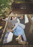 Man and woman relaxing with happiness emotion on net cradle over flowing creek stock photos