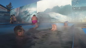 Man and woman relaxing in hot spring pool with natural thermal mineral water stock video