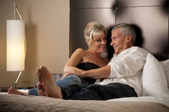 Man and Woman Relaxing in a Hotel Room Bed Stock Images