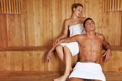 Man and woman relaxing in sauna. Attractive men and beautiful women relaxing together in sauna Royalty Free Stock Image