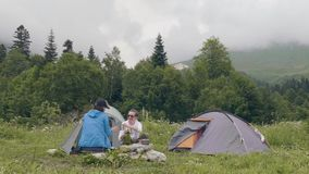 Man and woman resting on camping tent and mountain landscape background stock footage