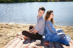 Man and woman resting outdoor. Young lovely couple resting on beach, handsome men and cute women sitting back to back on coast river, happy family concept Stock Images
