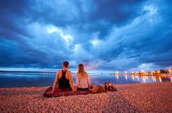 Man and woman resting on pebble beach at dusk on calm water dramatic blue cloudy sky background stock photography