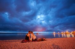 Man and woman resting on pebble beach at dusk on calm water dramatic blue cloudy sky background stock photo