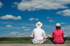 Man and woman resting sitting on the dock in the background of nature stock photos