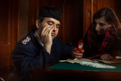 Man and woman in retro style weep over the manuscripts. Stock Images