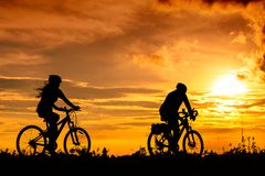 A man and a woman ride bicycles on the road with beautiful colorful sunset sky stock image