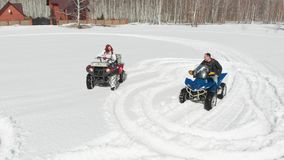 A man and a woman ride quad bikes one after another through the snow. Shot from the drone stock video footage