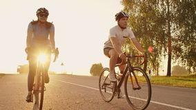 A man and a woman ride sports bikes on the highway at sunset in gear and protective helmets in slow motion 120 fps.  stock footage