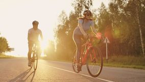 A man and a woman ride sports bikes on the highway at sunset in gear and protective helmets in slow motion 120 fps.  stock video