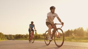 A man and a woman ride sports bikes on the highway at sunset in gear and protective helmets in slow motion 120 fps.  stock video footage