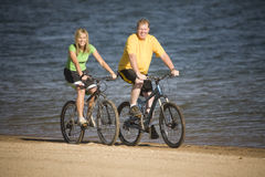 Man and woman riding bikes Stock Photos