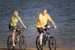 Man and woman riding bikes Stock Photos