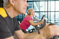 Man and woman riding exercise bikes in health club Stock Photos