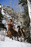 Man and Woman Riding Horses in the Snow Royalty Free Stock Photo