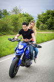 Man and woman riding motorcycle. Handsome young men riding motorcycle with women as passenger Royalty Free Stock Photo