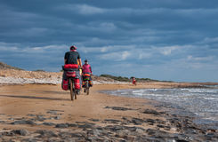 Man and woman riding sandy beach mountain bike with backpack. Stock Photography
