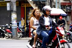 A man and a woman riding in tandem on a motorcycle in Antipolo City. Stock Photo